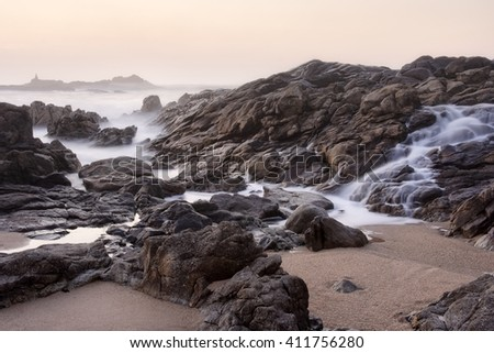 Rocky sea beach at sunset seeing a salt water cascade, north of Portugal. Long exposure. - stock photo