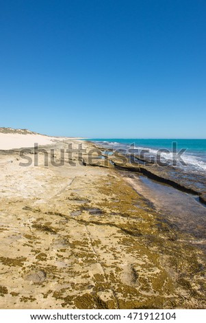 Rocky shore along Ningaloo Reef coast at Cape Range National Park, Exmouth, Western Australia, with beach, dunes, horizon, turquoise ocean water, blue sky and copy space.