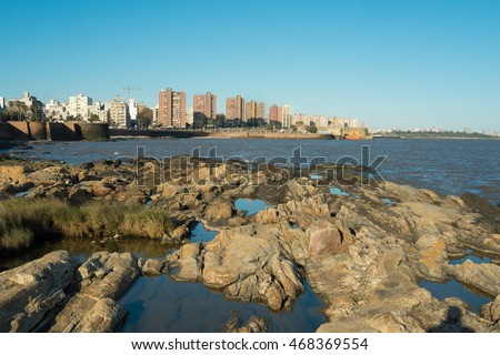 Rocky shore and the skyline of Montevideo in the background
