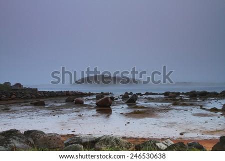 Rocky shore in rainy weather - stock photo
