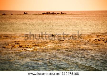 Rocky shore of the Mediterranean Sea. On the horizon, a natural stone breakwater. Toned. - stock photo