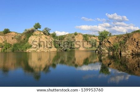 Rocky shore on blue lake - stock photo