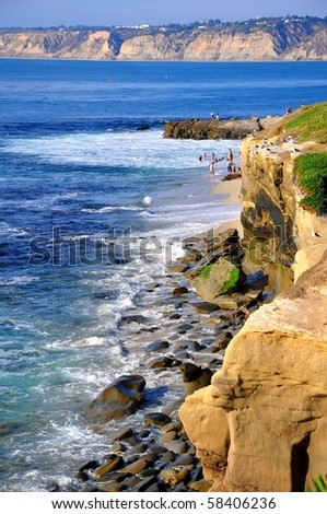 Rocky shore with bluffs in the distance, La Jolla. - stock photo