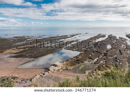 Rocky shore with tidal pools and reflections of the summer sky at the coast of St. Andrews, Scotland - stock photo
