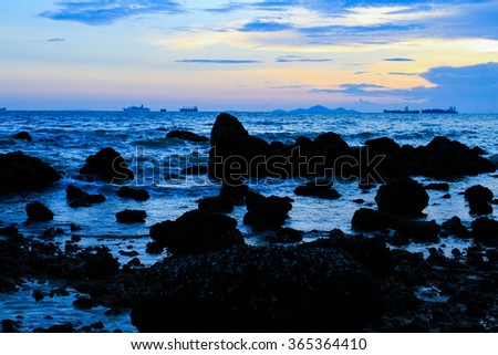 Rocky shoreline and and tide pools at sunset background - stock photo