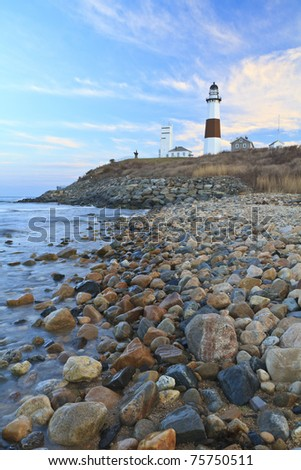 Rocky shoreline at sunset below Montauk Lighthouse at the Eastern end of Long Island, New York - stock photo