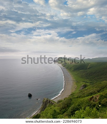 Rocky shores of the bay, covered with grass and trees, Primorye, Russia