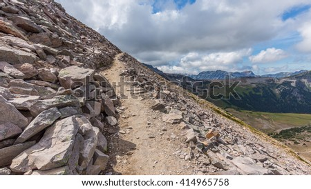 Rocky slopes in the mountains. Amazing view at the peaks which rose against the cloud sky. Path on the tops of mountains. BURROUGHS MOUNTAIN TRAIL, Sunrise Area, Mount Rainier National Park - stock photo