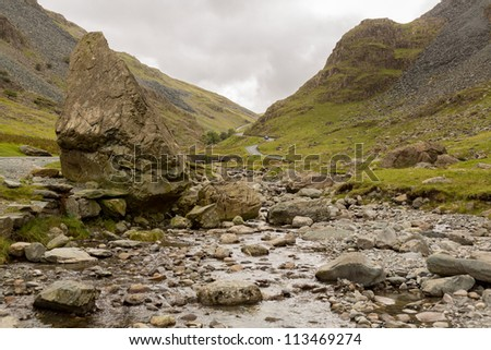 Rocky stream runs by steep road in Honister Pass in English Lake District - stock photo