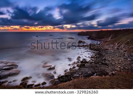 Rocky sunrise Magnificent sunrise view in the blue hour at the Black sea coast, Bulgaria - stock photo