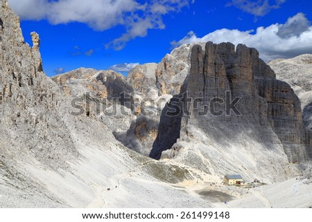 Rocky trail descending along sunny valley to Vajolet towers, Catinaccio massif, Dolomite Alps, Italy - stock photo