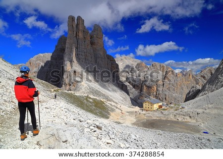 Rocky valley and woman climber watching the Vajolet towers in Catinaccio mountains, Dolomite Alps, Italy - stock photo