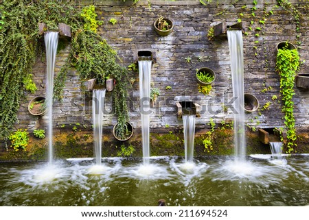 Rocky wall with small waterfalls in Planten un Blomen park in Hamburg, Germany - stock photo