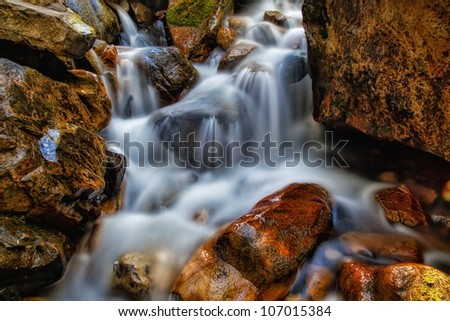 rocky waterfall with logs and large rocks/ Waterfalls/ Brown and Orange Boulders and Waterfalls - stock photo