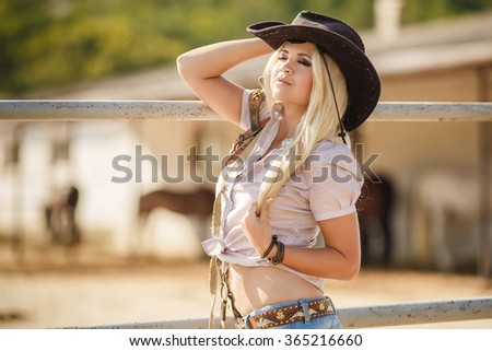 Rodeo, cowboy, western. Young, happy and sexy cowgirl in western style. Young sexy Woman wearing cowboy hat. outdoor fashion portrait cowgirl in hat in the western village. Woman portrait outdoor - stock photo