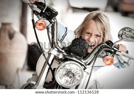Rogue Child riding a motorcycle - stock photo