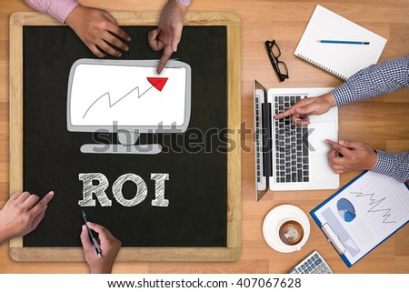 Roi Return On Investment Analysis Concept Businessman working at office desk and using computer and objects on the right, coffee,  top view, - stock photo