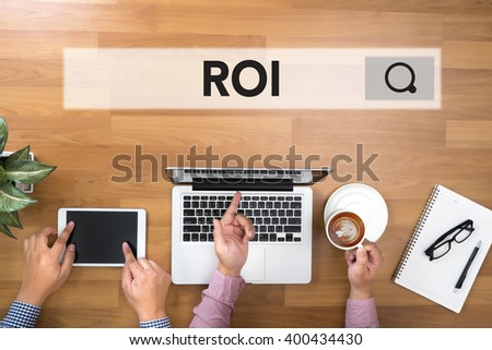 Roi Return On Investment Analysis Concept Two Businessman working at office desk and using a digital touch screen tablet and use computer - stock photo
