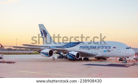 ROISSY, FRANCE --SEPTEMBER 2014-- A jumbo Airbus A 380 from Malaysia Airlines is parked at the gate in the Roissy Charles de Gaulle international airport (CDG), in the suburbs of Paris, France. - stock photo