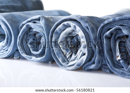 roll blue denim jeans arranged in line, isolated on white - stock photo