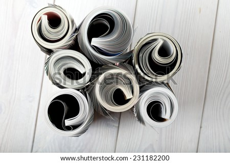 Roll newspaper and magazine. close up front view of magazine Roll on white wood background - stock photo