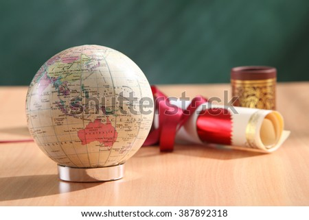 roll of certificate and desk globe - stock photo
