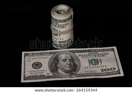 Roll of $100 dollar bills and a loose bill on black background - stock photo