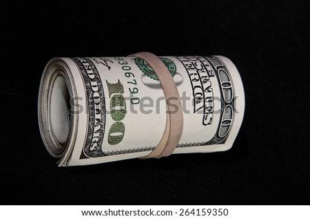 Roll of $100 dollar bills on black background - stock photo