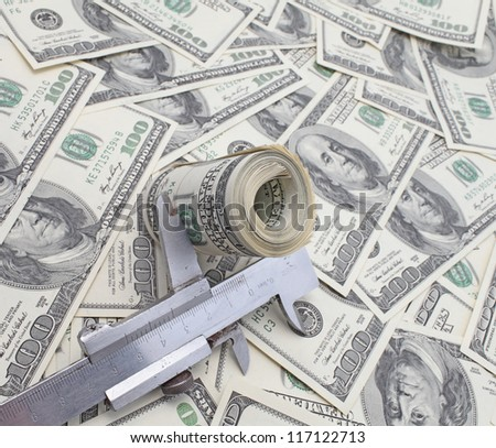 roll of dollars in Calipers against 100 dollar bills.