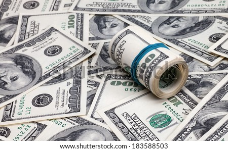 Roll of dollars on a background of American dollar bills