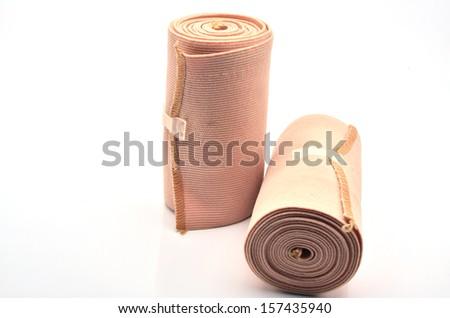 Roll of Elastic Crepe Bandage Lying on White Background - stock photo