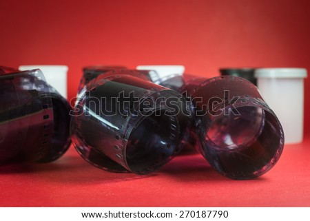 Roll of Film Unwound with Film Canisters on Red Background