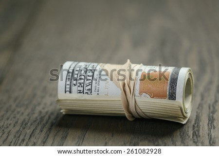 roll of hundred dollar bills on wooden table - stock photo