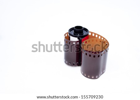 Roll of 35mm photographic film extending from casing - stock photo