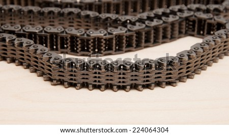 Roll of motor chains arranged on a wooden table.