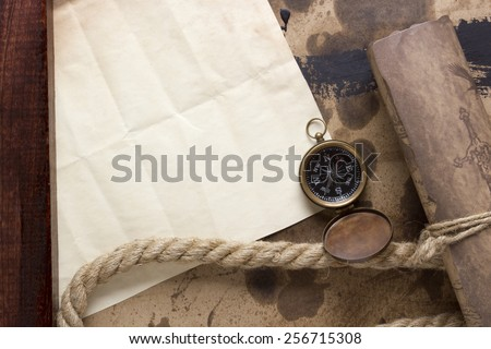 Roll of parchment with a compass and marine rope. - stock photo