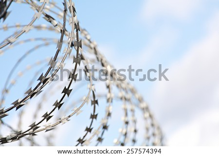 roll of reinforced barbed tape cutter, blurred in the background, copy space in the blue sky with clouds - stock photo