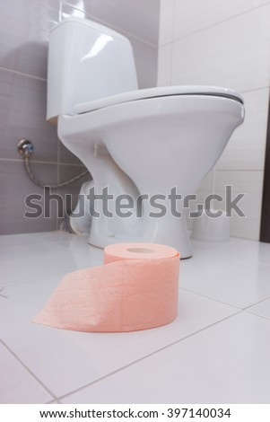 Roll of soft pink toilet paper in a bathroom standing on a white tiled floor near a plain white wc or toilet fixture, low angle view - stock photo
