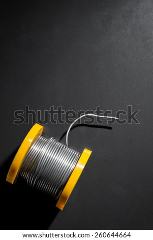 Roll of soldering wire on a dark background. - stock photo
