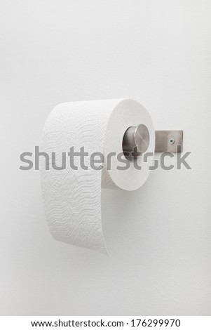 Roll of white toilet paper on a silver metal wall-mounted holder, close up view on a plain white wall in a bathroom