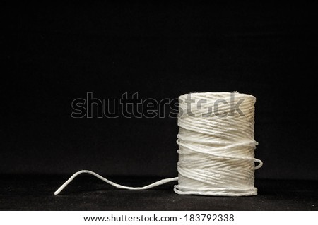Roll of White Twine on a Black Background - stock photo
