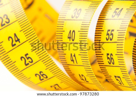 Roll of yellow measuring tape rolled up over white background