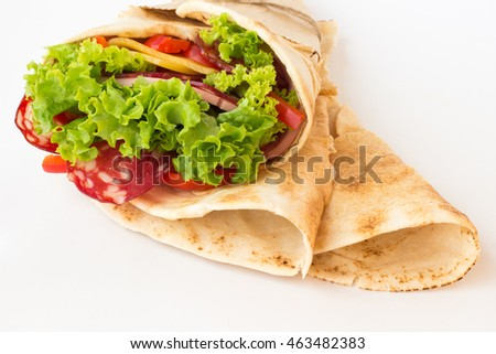 Roll tortilla with herbs, cheese and meat on a white background