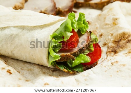 roll with meat and salad in pita bread