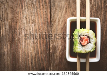 Roll with sauce and sticks on wooden table close up - stock photo