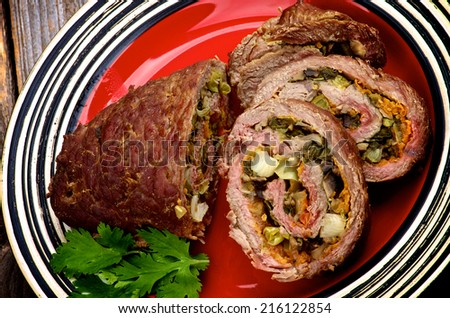 Rolled Beef Meatloaf Stuffed with Leek, Carrot and Greens Half and Slices on Red Plate - stock photo