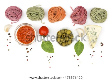 Rolled colored pasta, vegetables and spices as a food background