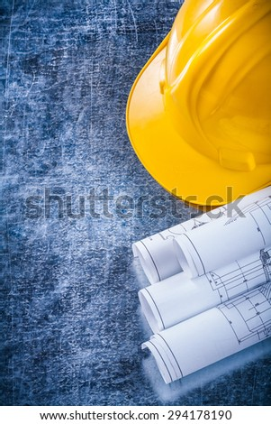 Rolled construction plans and yellow hard hat on metallic scratched surface building and architecture concept. - stock photo