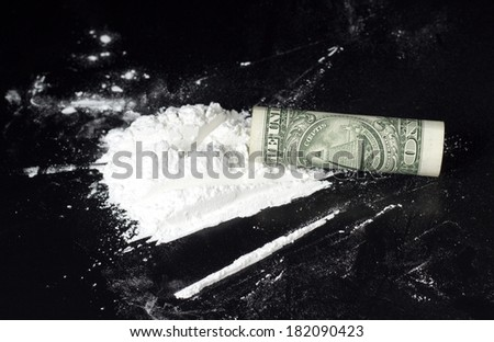 rolled dollar with cocaine heap on black table