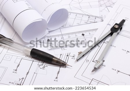 Rolled electrical diagrams and accessories for drawing lying on construction drawing of house, drawings and accessories for the projects engineer jobs - stock photo